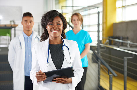 Portrait of a friendly female african american doctor and team in bright modern office